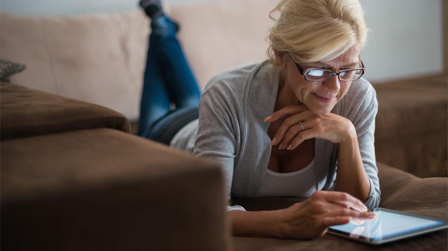 Femme sur sa tablette en train de faire des réglages pour son logement connecté