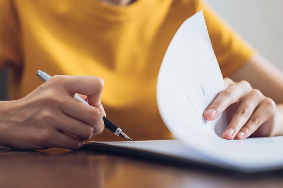 Femme signant son mandat de vente