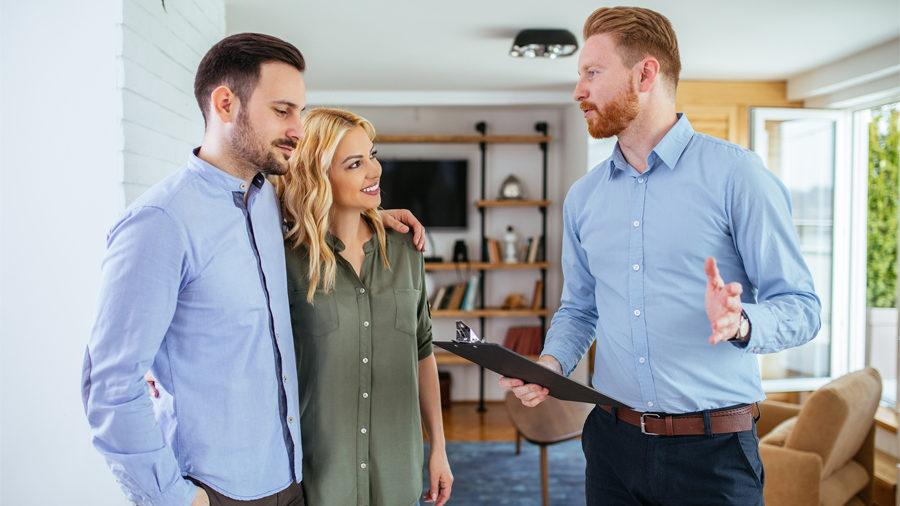 Couple avec un agent immobilier pour estimer leur bien