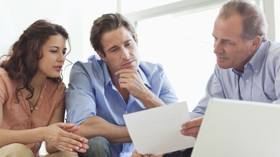 Couple avec agent immobilier qui leur explique les démarches pour vendre leur bien