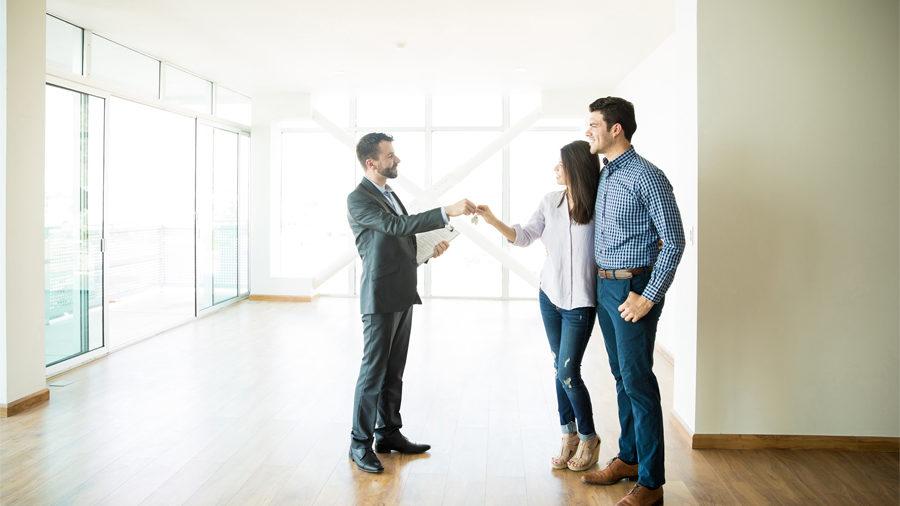 Agent immobilier remettant les clés d'un appartement à un couple